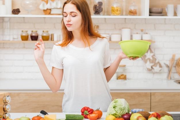 Estilo de vida saudável. receita de perda de peso. jovem mulher com saladeira, olhando para a variedade de vegetais orgânicos.