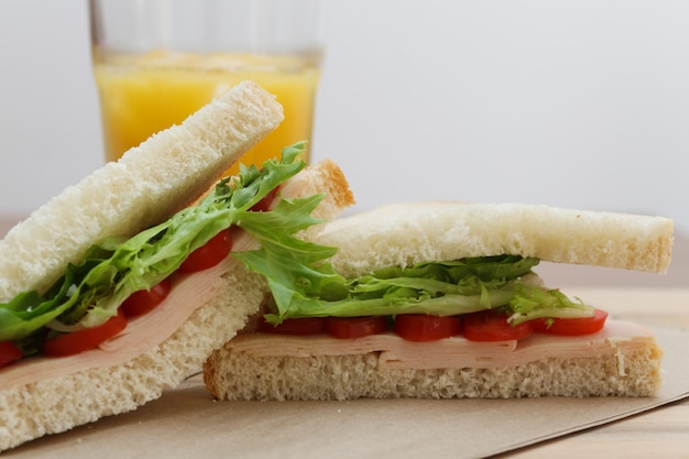 Estilo de vida saudável: sanduíche de peru na placa de madeira e um copo de suco de laranja
