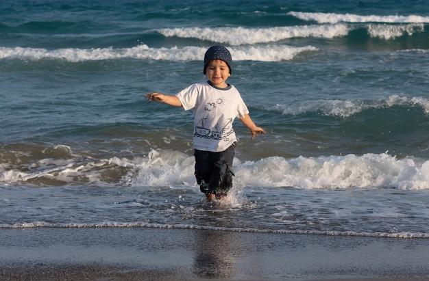Estilo de vida saudável. um menino caminha e brinca à beira-mar.