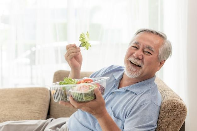 Estilo de vida sênior homem se sentir feliz desfrutar de comer salada fresca de comida de dieta no sofá