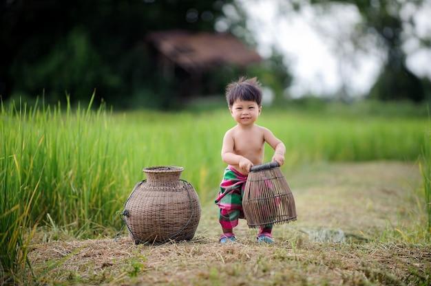 Estilo de vida tailandês do bebê para fora porta na natureza.