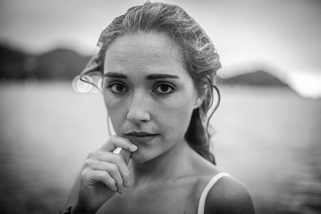 Estilo de vida, uma jovem loira com biquíni branco por dentro com cabelo molhado, foto preto e branco
