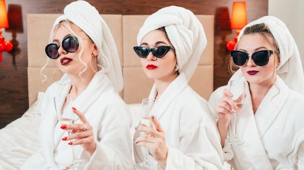 Estilo de vida urbano das mulheres. cuidado e luxo. rostos de autoconfiança. champanhe nas mãos. vestidos com óculos de sol, roupão e turbante.