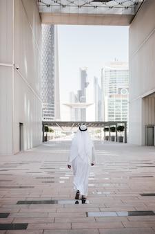 Estilo de vida urbano dos emirados na cidade grande com um investidor árabe verificando a cidade no país do golfo.