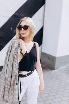 Estilo de vida urbano moda retrato da moda da jovem garota loira cute vestida com roupas preto e brancas, andando na cidade em dia de verão em óculos de sol