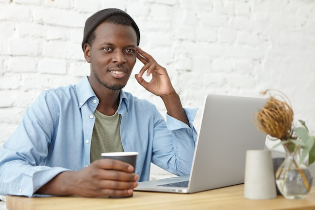 Estilo de vida urbano moderno e conceito de tecnologias. atraente jovem afro-americano masculino freelancer usando chapéu tendo café enquanto trabalhava remotamente no laptop pc, pensativo ou sonhador