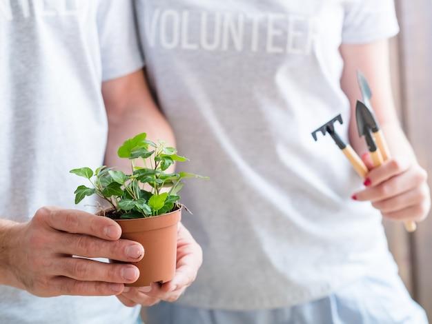 Estilo de vida voluntário. pense no conceito verde. casal com planta de casa e ferramentas de jardim.