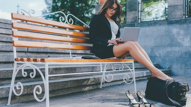 Estilo de vida workaholic. tecnologia moderna. mulher ocupada, sentado no banco, trabalhando no laptop.