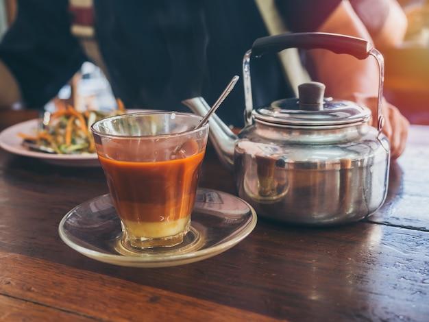 Estilo do sul tailandês do café da manhã, chá tailandês quente na chaleira do vidro e do vintage na tabela de madeira.