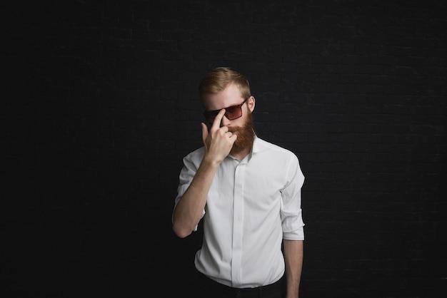 Estilo e conceito de moda. bonito na moda jovem com barba ruiva posando com roupa formal, ajustando os elegantes óculos de sol, tendo uma expressão confiante