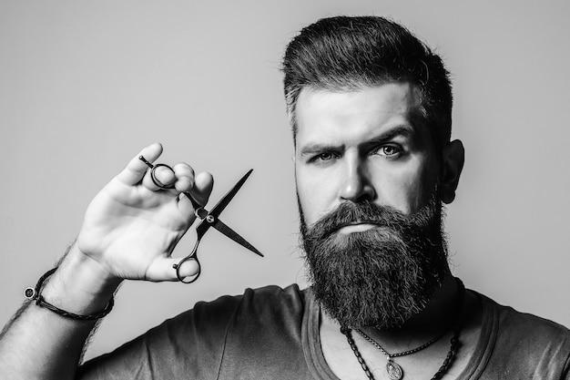 Estilo e corte de barba. homem barbeiro brutal segurando ferramentas profissionais.