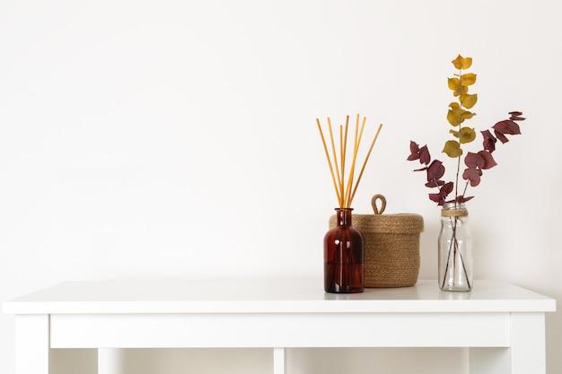 Estilo escandinavo hygge, difusor de aroma interior com varas de madeira, cesta de palha, galhos secos de eucalipto
