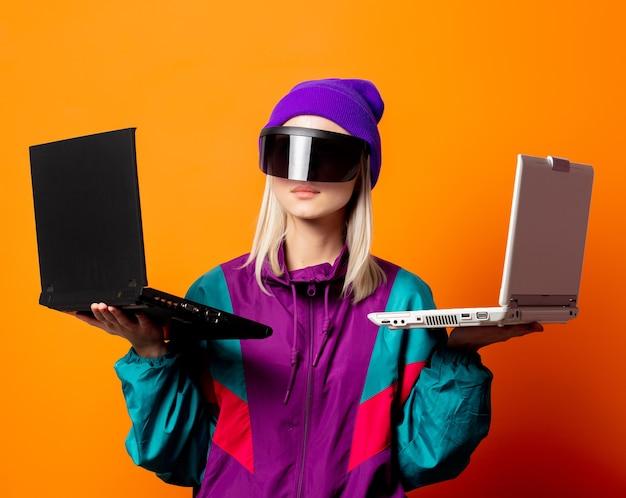 Estilo feminino com agasalho de treino dos anos 90 com óculos de realidade virtual e notebooks em laranja