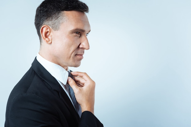 Estilo formal. agradável alegre bom empresário tocando sua gravata e consertando enquanto se arruma para o trabalho