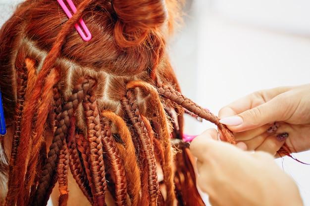Estilo hippie penteado cabeleireiro mãos trança garotas ruivas tranças rabo de cavalo brilhante na cabeça