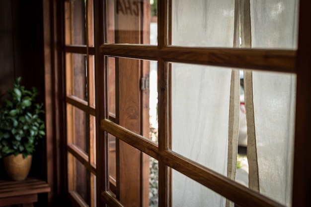 Estilo japonês, janela com tecido branco na frente de reatuarant e aro de luz feito de madeira