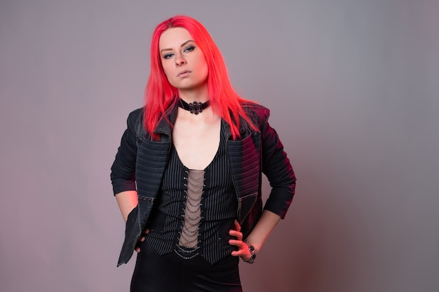 Estilo kitsch, moda do futuro. misturar estilos. uma jovem com cabelos escarlates brilhantes e roupas escuras incomuns em um fundo cinza