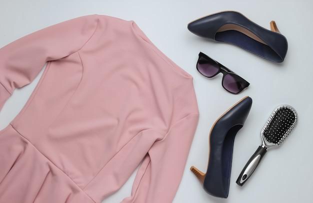 Estilo liso, acessórios de roupas femininas em um fundo branco pente de óculos de sol de sapatos de salto alto de couro vestido rosa