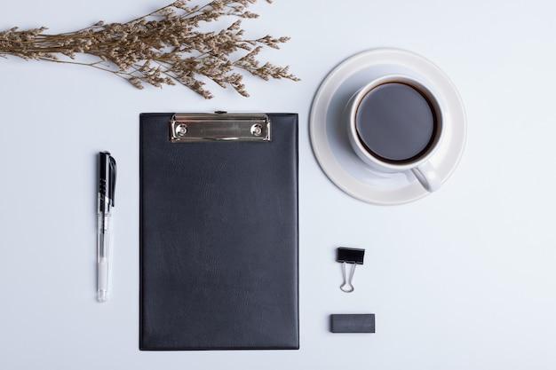Estilo liso leigo, vista superior moderno escritório branco mesa desk.black livro, copo branco café, caneta, borracha e flor seca em branco
