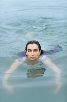 Estilo livre nadando no mar em traje de banho branco