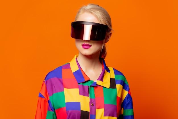 Estilo loira com roupas dos anos 90 e óculos de realidade virtual laranja