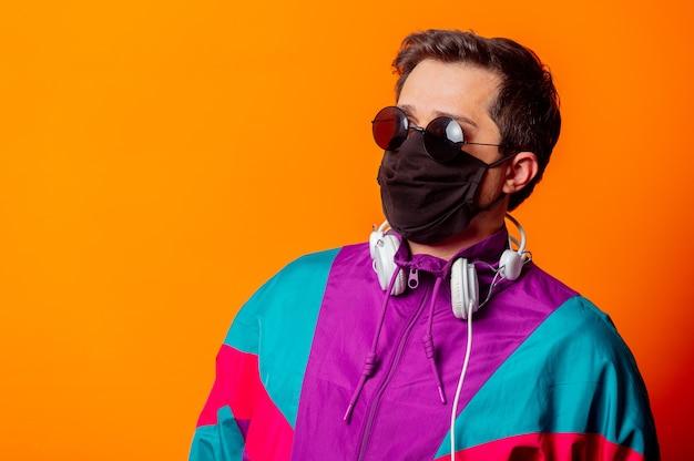 Estilo masculino com máscara facial e agasalho esportivo dos anos 80 com fones de ouvido