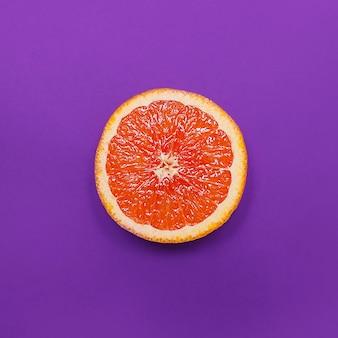 Estilo minimalista, laranja de layout criativo e toranja no fundo roxo