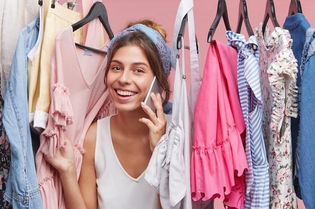 Estilo, moda, compras e consumismo. animado jovem encantadora usando bandana falando no telefone móvel entre itens de roupas da moda no camarim da loja, dizendo a amigo sobre a venda final