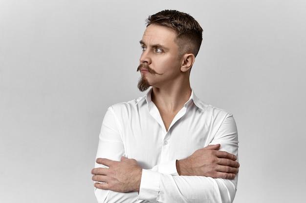 Estilo, moda e conceito de negócios. imagem de estúdio de um jovem empresário europeu elegante e confiante com bigode e barba elegantes, cruzando os braços sobre o peito e olhando para longe, com olhar pensativo