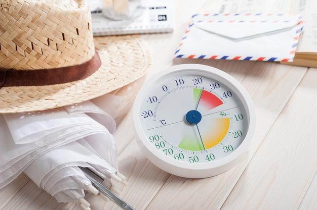 Estilo moderno branco de termômetro e higrômetro analógico com outros objetos na prancha de madeira branca