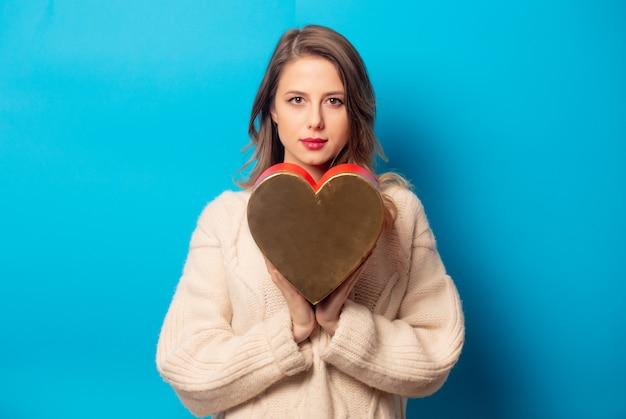 Estilo mulher de camisola com caixa de presente na parede azul