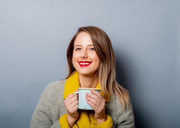 Estilo mulher de casaco com uma xícara de café