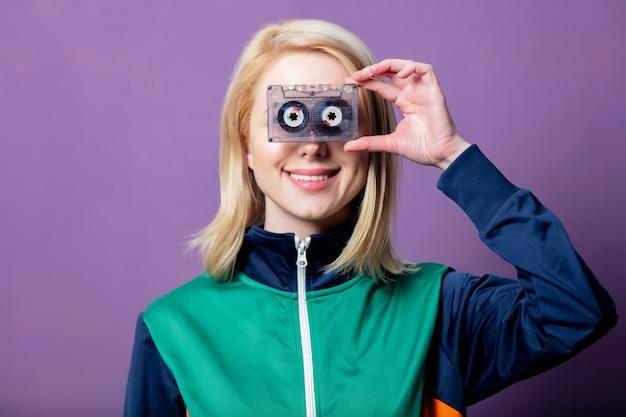 Estilo mulher loira em roupas dos anos 80 com fita cassete