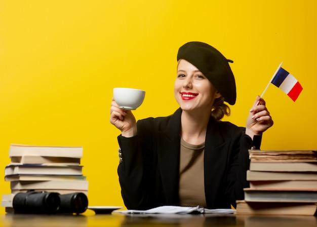 Estilo mulher loira na boina com bandeira francesa e livros em amarelo
