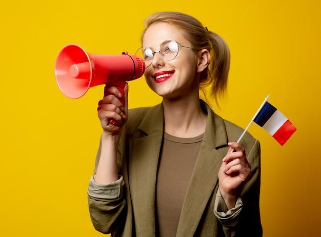 Estilo mulher loira na jaqueta com bandeira francesa e megafone em amarelo