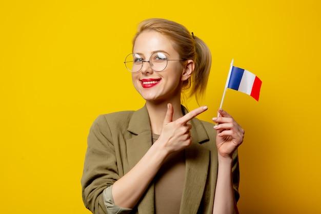 Estilo mulher loira na jaqueta com bandeira francesa em amarelo