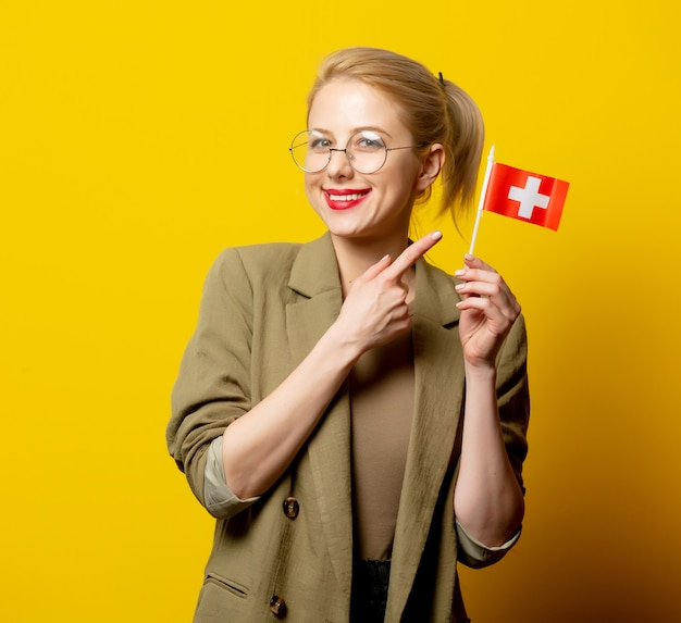 Estilo mulher loira no casaco com a bandeira da suíça em amarelo