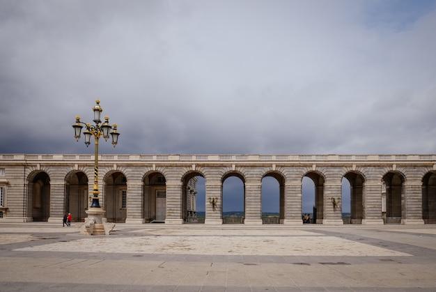Estilo neoclássico de arcos na praça da plaza de la armeria em dia chuvoso. madri, espanha.