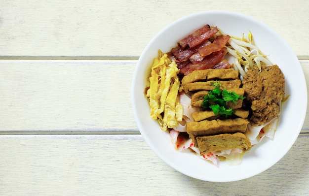 Estilo noodle china com ovo, salsicha, tofu, carne de porco ontop com molho cinza