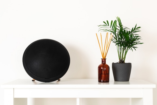 Estilo nórdico hygge escandinavo, interior de casa, planta verde, alto-falante portátil, difusor de aromas de perfume, prateleira branca