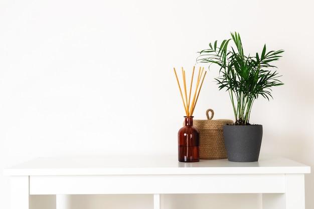 Estilo nórdico hygge escandinavo, planta verde interior de casa, difusor de aromas perfumados, cesta de palha pequena, prateleira branca
