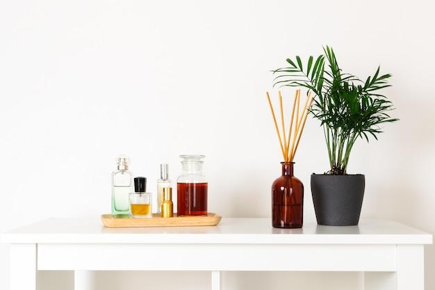 Estilo nórdico hygge escandinavo, planta verde interior de casa, difusor de aromas perfumados, perfumes, bandeja de madeira, prateleira branca