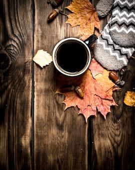 Estilo outono uma xícara de café quente com luvas em uma mesa de madeira