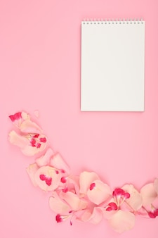Estilo plano colocar maquete com elementos florais na mesa-de-rosa. copie o espaço.
