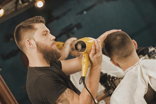 Estilo por profissional. retrato de um barbeiro, secando o cabelo de seu cliente, usando um secador de cabelo
