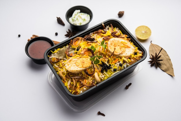 Estilo restaurante egg biryani ou anda pulao embalado para entrega ao domicílio em caixa de plástico ou recipiente com raita e salan