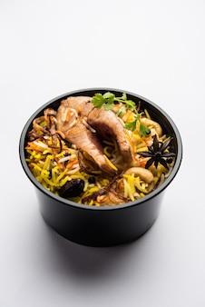Estilo restaurante peixe biryani ou pulao embalado para entrega ao domicílio em caixa de plástico ou recipiente com raita e salan