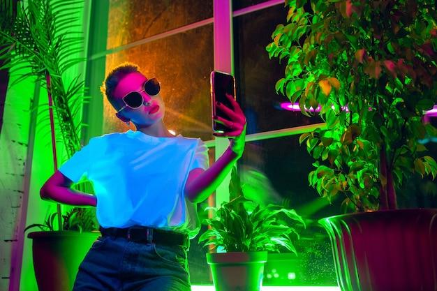 Estilo. retrato cinematográfico de mulher elegante no interior iluminado por néon. tons de efeitos de cinema, cores neon brilhantes. modelo caucasiano usando smartphone em luzes coloridas dentro de casa. cultura jovem.