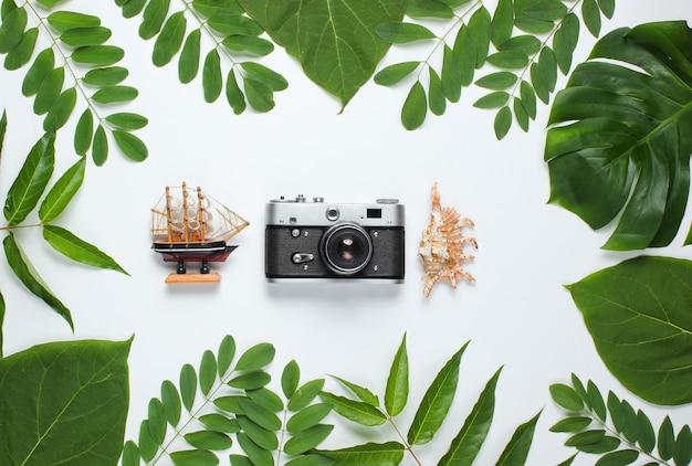Estilo retro ainda vida de viagens. câmera de filme, conchas, folhas tropicais verdes. acessórios para viajantes em um fundo branco.