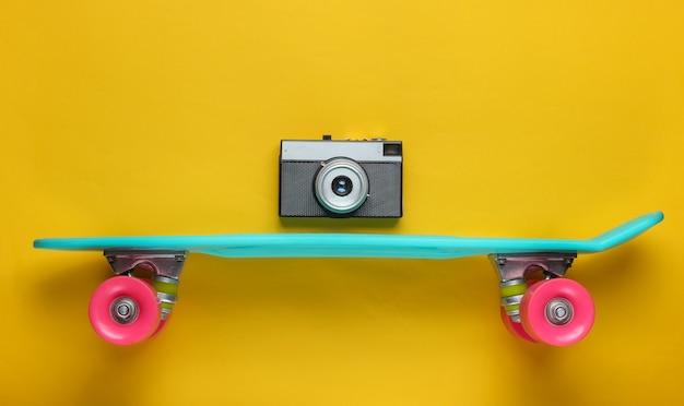 Estilo retrô. mini placa cruiser de plástico e câmera retro em fundo amarelo. tendência de cores pastel. diversão de verão. conceito minimalista da juventude.